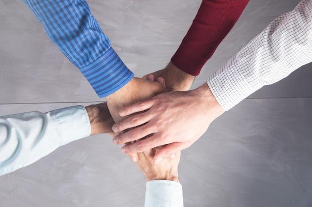 Grupo de personas manos unidas para construir el trabajo en equipo junto con spirit