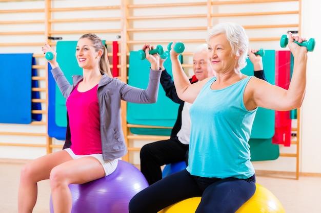 Grupo de personas mayores y jóvenes en fisioterapia haciendo ejercicios.