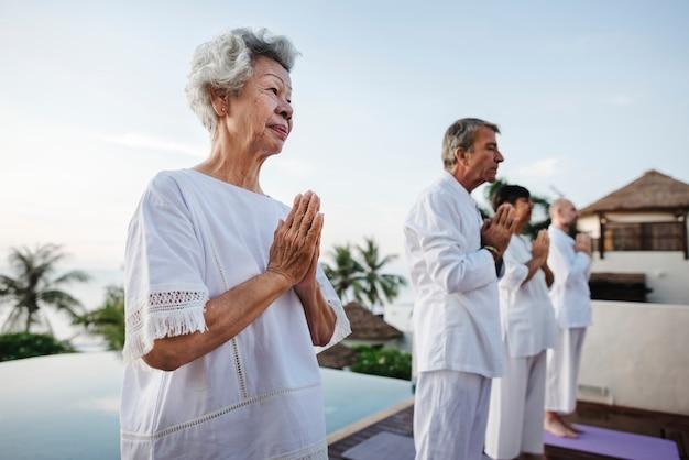 Grupo de personas mayores practicando yoga junto a la piscina.