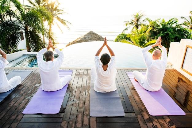 Grupo de personas mayores practicando yoga en la mañana.