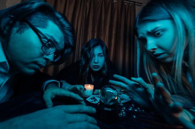 Grupo de personas y mujer adivina con bola de cristal
