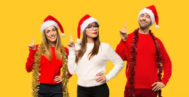 Un grupo de personas mujer rubia vestida para las vacaciones navideñas mostrando el pulgar hacia abajo