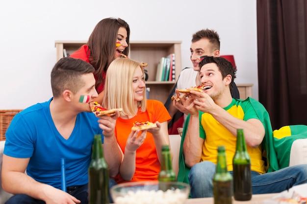 Grupo de personas multinacionales comiendo pizza durante el descanso en el partido de fútbol