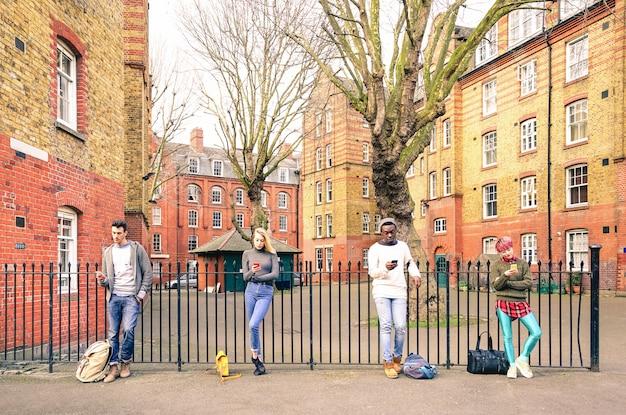 Grupo de personas multirraciales y amigos urbanos que usan un teléfono inteligente cerca de shoreditch londres