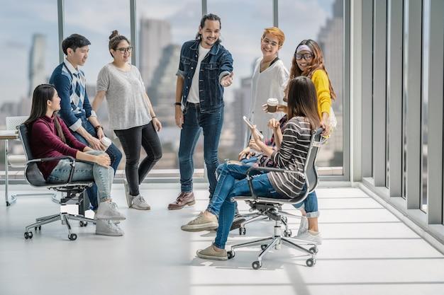 Grupo de personas de negocios asiáticas y multiétnicas con trajes casuales que hablan e intercambian ideas.