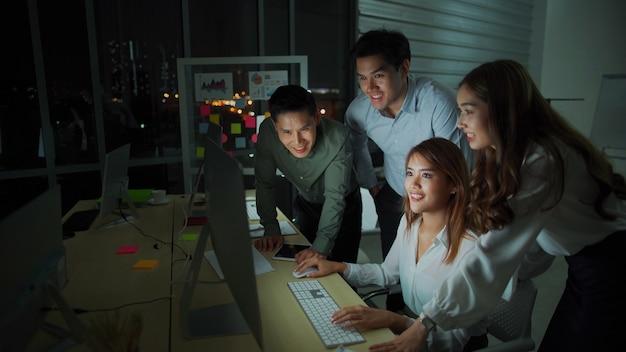 Grupo de personas de negocios de diversidad equipo trabajando hasta tarde en la oficina por la noche. dos hombres caucásicos y una niña asiática se sienten felices y exitosos para nuevos negocios. trabajo nocturno y concepto de horas extra