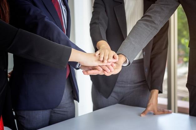 Grupo de personas de negocios poniendo las manos juntas.