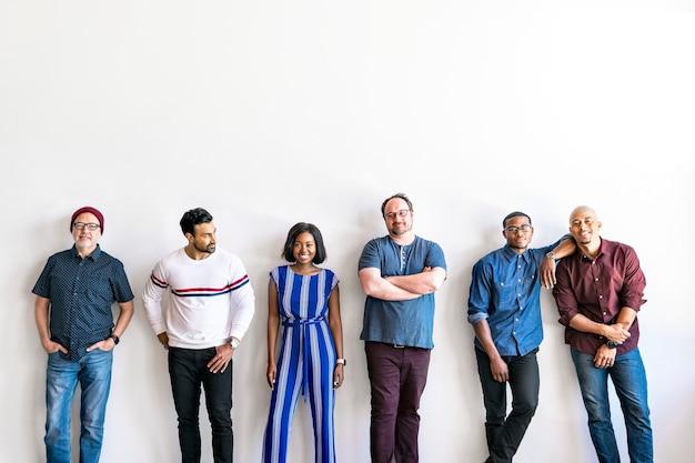 Grupo de personas de pie en un por una pared blanca