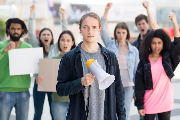 Grupo de personas protestando y usando megáfonos