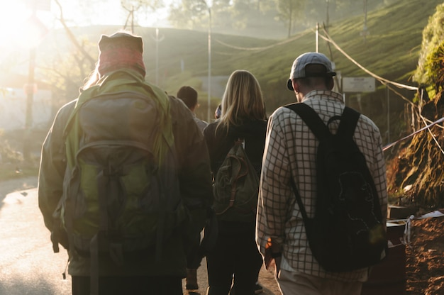 Grupo de personas que camina por el camino en luz del sol hermosa. primer plano vista posterior