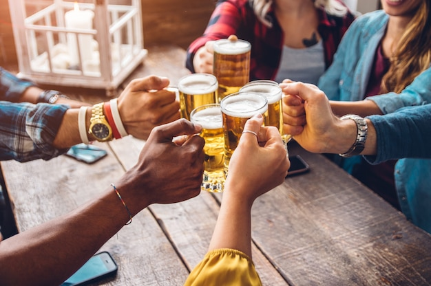 Grupo de personas que disfrutan y tuestan una cerveza en cervecería pub - concepto de amistad con jóvenes que se divierten juntos