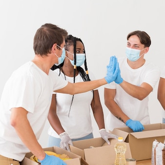 Grupo de personas que forman un buen equipo mientras se ofrecen como voluntarios