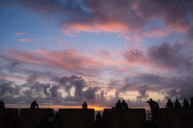 Grupo de personas que mira puesta del sol con las nubes y el cielo hermosos en el período crepuscular.