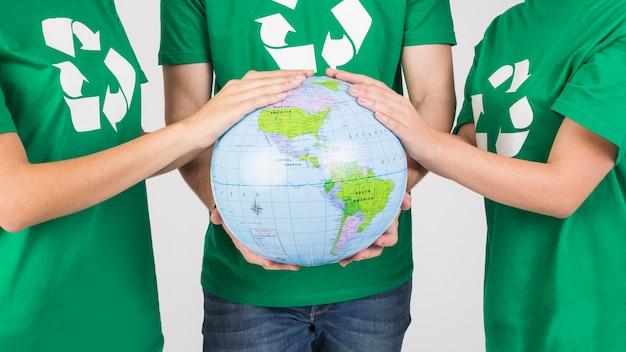 Grupo de personas que sostiene el globo en las manos juntas