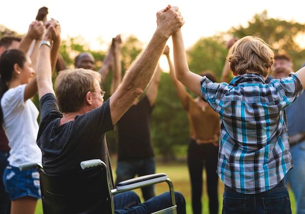 Grupo de personas que sostienen la unidad del equipo de manos