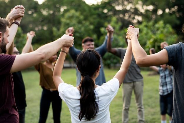 Grupo de personas que sostienen la unidad del equipo de soporte de manos.