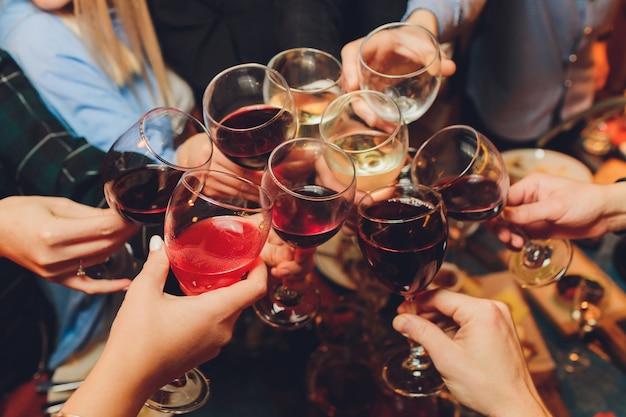 Grupo de personas que tintinean vasos con vino o champán