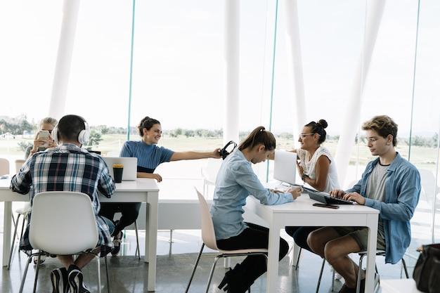 Grupo de personas que trabajan en mesas separadas en un coworking con computadoras portátiles, móviles y café.