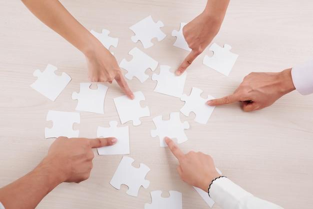 Grupo de personas recogiendo rompecabezas