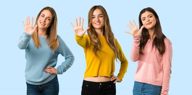 Grupo de personas con ropa colorida contando cinco con los dedos sobre fondo colorido