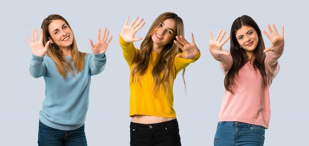 Grupo de personas con ropa colorida contando diez con los dedos sobre fondo colorido