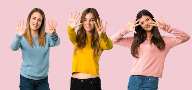 Grupo de personas con ropa colorida contando nueve con los dedos sobre fondo colorido