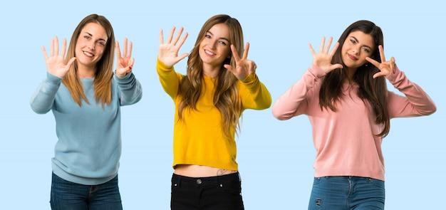 Grupo de personas con ropa colorida contando ocho con los dedos sobre fondo colorido