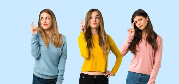 Grupo de personas con ropa colorida con dedos cruzándose y deseando lo mejor.