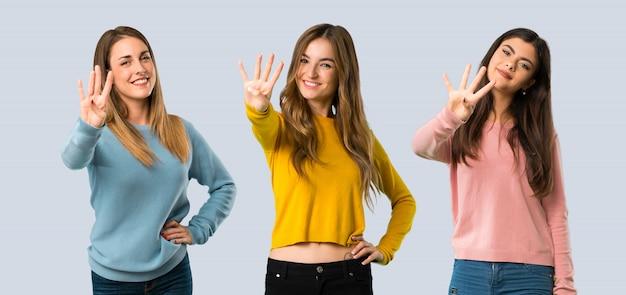 Grupo de personas con ropa colorida feliz y contando cuatro con los dedos.