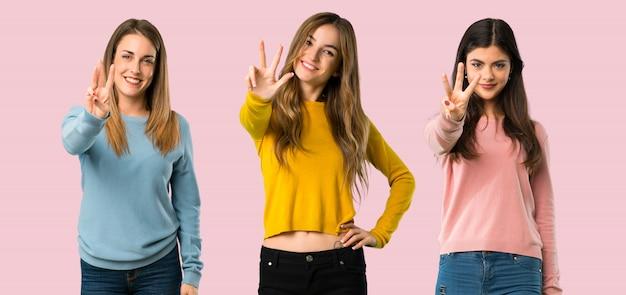 Grupo de personas con ropa colorida feliz y contando tres con los dedos.