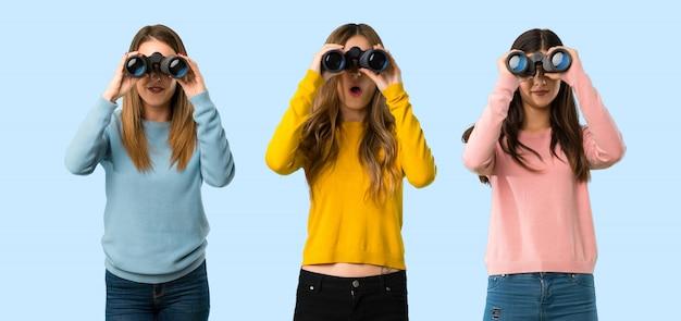 Grupo de personas con ropa colorida y mirando en la distancia con binoculares