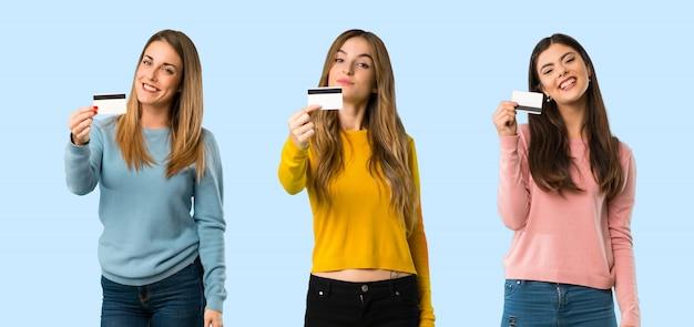 Grupo de personas con ropa colorida que sostiene una tarjeta de crédito en fondo colorido