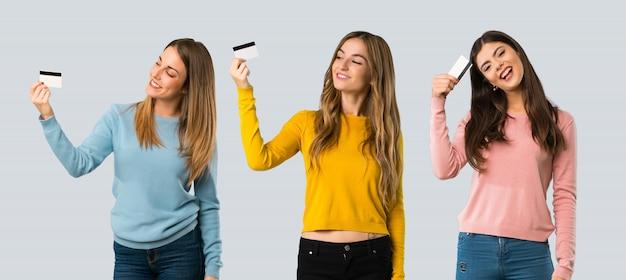 Grupo de personas con ropa colorida que sostiene una tarjeta de crédito y que piensa en fondo colorido