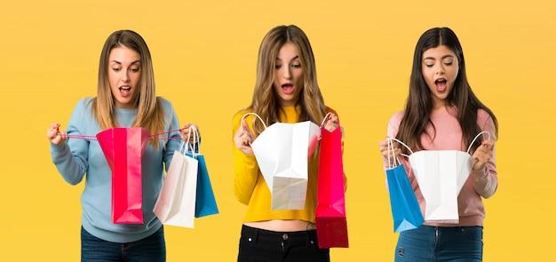 Grupo de personas con ropa colorida sorprendida mientras sostiene una gran cantidad de bolsas de compras