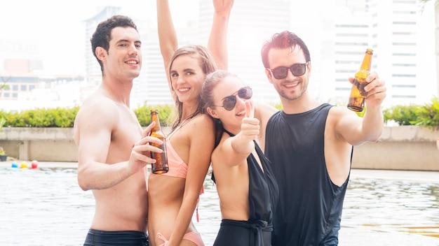 Grupo de personas en ropa de verano bailando junto a la piscina con botellas de cerveza
