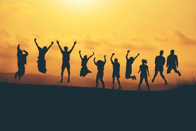 Grupo de personas saltando sobre la puesta de sol de montaña, fiesta de amigos, tiempo feliz