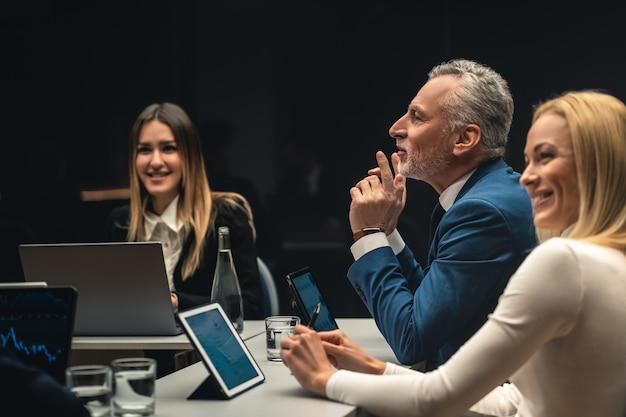 El grupo de personas sentadas a la mesa en una conferencia de negocios.