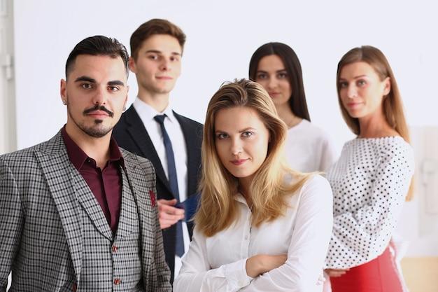 Grupo de personas sonrientes de pie en la oficina mirando en la cámara