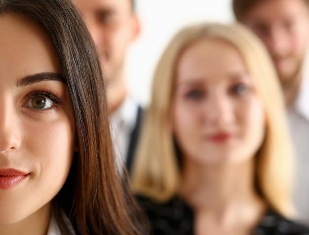 Grupo de personas sonrientes de pie en la oficina mirando