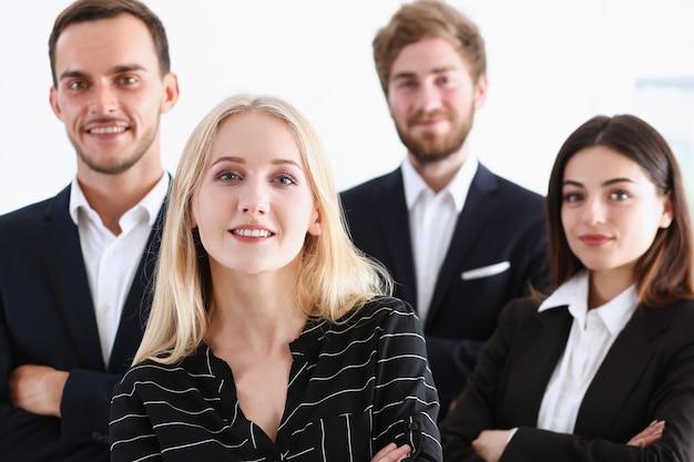 Grupo de personas sonrientes de pie en la oficina posando