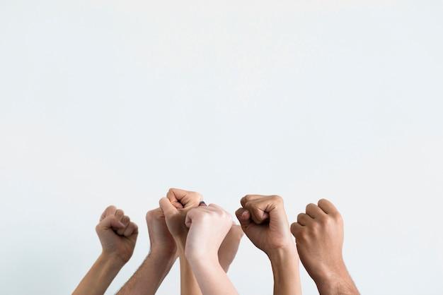 Grupo de personas sosteniendo los puños