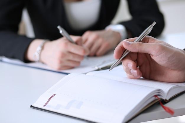 El grupo de personas sostiene la pluma de plata lista para hacer nota en primer abierto de la hoja del cuaderno.