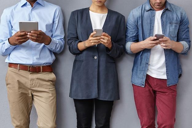 Grupo de personas con teléfonos inteligentes y tabletas.