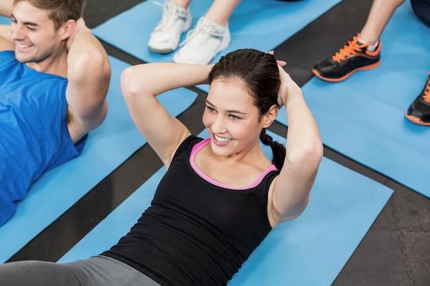 Grupo de personas trabajando sus abdominales en el gimnasio.