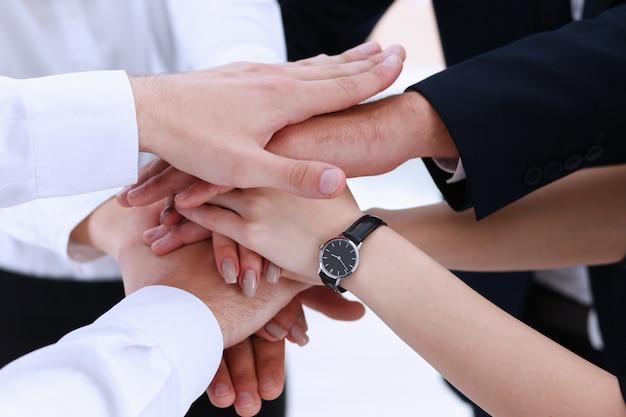 Grupo de personas en trajes de manos cruzadas en la pila