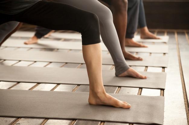 Grupo de personas yoguis en guerrero dos piernas de cerca