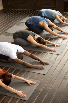 Grupo de personas yoguis en pose balasana