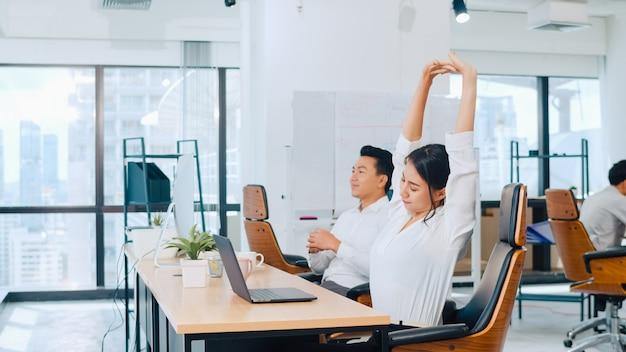 Grupo de proceso colaborativo de empresarios multiculturales en ropa casual elegante que se comunican y usan tecnología mientras trabajan juntos en una oficina creativa. el equipo asiático de jóvenes profesionales trabaja.