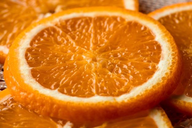 Grupo de rodajas de naranja fresca y mitades de las frutas sobre una tabla de cortar de madera en la mesa de la cocina cortada por ama de casa para comer