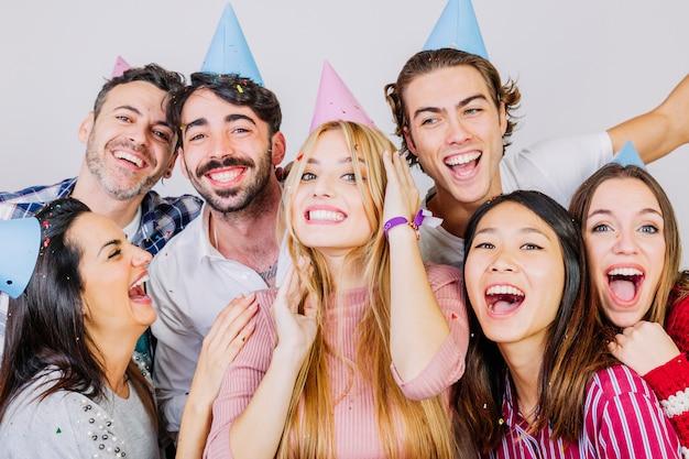 Grupo de siete amigos jóvenes celebrando cumpleaños